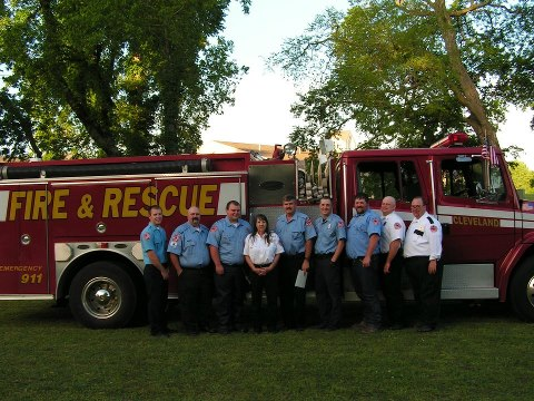 Nine members of a fire department staff standing near a fire truck