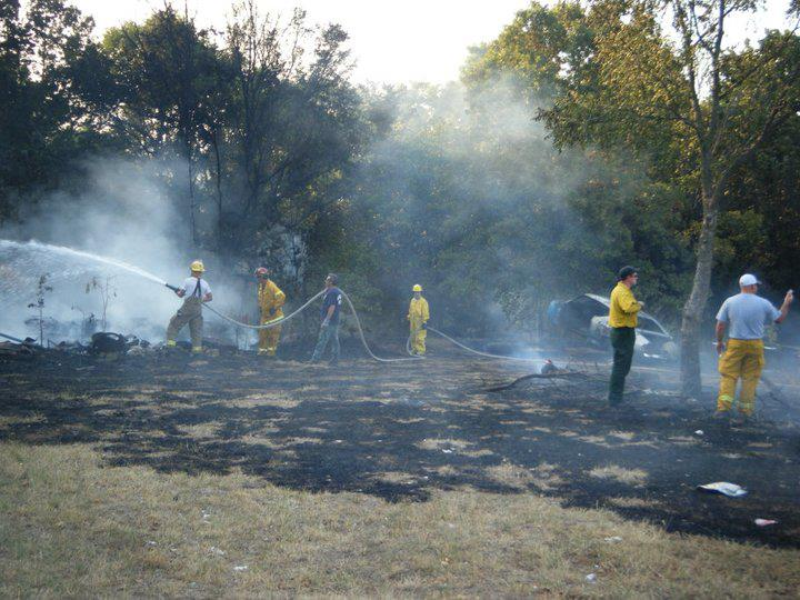 A group of fire personnel holding a long fire hose extinguishing a fire in a wooded area