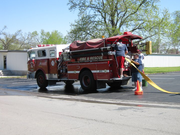 Three men putting a fire hose back into a fire truck in a parking lot